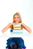 Smiling teen girl holding hands on piles of books Royalty Free Stock Photos