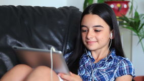 Smiling teen girl listening to music on tablet pc Royalty Free Stock Image