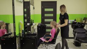Adorable girl visiting hairstylist in barber shop stock footage