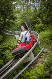 Smiling teen girl riding downhill on an outdoor roller coaster on a warm summer day. royalty free stock photography