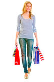 Smiling teen girl with shopping bags making step Stock Image