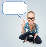 Smiling teen girl sitting on floor with tablet pc. Communication, technology, internet, gesture and people concept - smiling teenage girl in eyeglasses holding Stock Photo