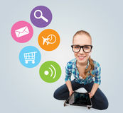 Smiling teen girl sitting on floor with tablet pc Stock Photos