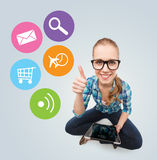 Smiling teen girl sitting on floor with tablet pc Stock Images