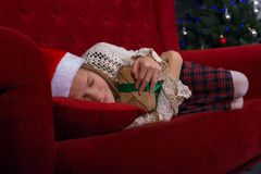 Smiling teen girl is sleeping sweetly on a merry Christmas. Smiling teen girl is sleeping sweetly on the couch near a Christmas tree, with gifts in her hands Stock Photos