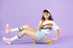 Smiling teen girl in vivid clothes, glasses sitting on skateboard, hold something, pointing hand on camera isolated on royalty free stock photo