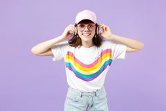 Smiling teen girl in vivid clothes, heart eyeglasses listening music with headphones isolated on violet pastel wall royalty free stock photos