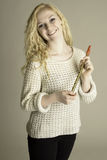 Smiling teen holding pennywhistle. Smiling and healthy teen holding a pennywhistle wearing white sweater black jeans stock photos