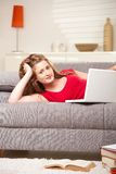 Smiling teen with laptop on sofa at home Stock Images