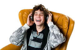 Smiling teen listening to music. Teen boy  listening to music with his headphones laughing with his eyes closed Stock Photo