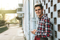 Smiling teen portrait. Portrait of smiling teen boy leaning against wall on urban sidewalk Royalty Free Stock Photography