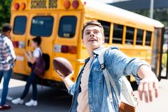 smiling teen schoolboy throwing american football ball in front of