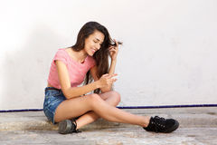 Smiling teen sitting outside looking at mobile phone Royalty Free Stock Image