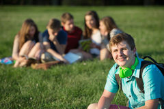 Smiling Teen Student. With earphones sitting outdoors Royalty Free Stock Image