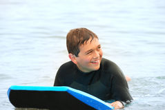 Smiling Teen Surfer. Smiling teenage surfer laying on his bodyboard in the ocean Stock Images