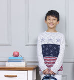 Smiling teenage Asian boy holding book bag standing beside desk. Little Chinese boy standing smiling beside books & apple on desk Stock Photos