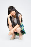 Smiling teenage asian girl sitting Royalty Free Stock Images