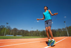 Smiling teenage athlete skipping the rope outside Royalty Free Stock Image