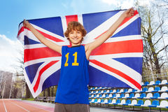 Smiling teenage boy with British flag on a stadium. Close-up portrait of happy smiling teenage boy in sportswear holding flag of Great Britain behind him outside Stock Images