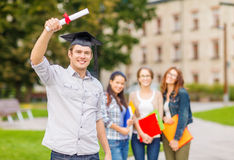 Smiling teenage boy in corner-cap with diploma Royalty Free Stock Image