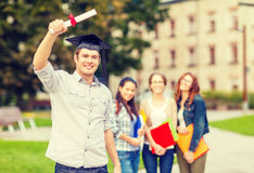 Smiling teenage boy in corner-cap with diploma Stock Image