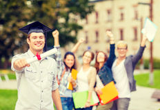 Smiling teenage boy in corner-cap with diploma Stock Photos