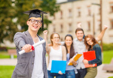 Smiling teenage boy in corner-cap with diploma Royalty Free Stock Images