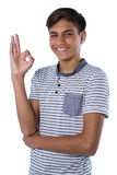 Smiling teenage boy gesturing okay hand sign. Against white background Stock Photography