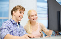 Smiling teenage boy and girl in computer class. Technology, school and education concept - smiling teenage boy and girl in computer class at school Royalty Free Stock Image