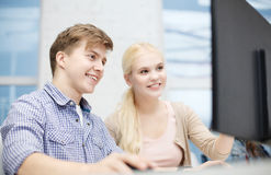 Smiling teenage boy and girl in computer class. Technology, school and education concept - smiling teenage boy and girl in computer class at school Royalty Free Stock Images