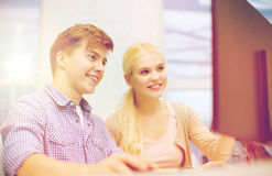 Smiling teenage boy and girl in computer class. Technology, school and education concept - smiling teenage boy and girl in computer class at school Stock Images