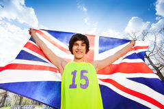 Smiling teenage boy holding flag of Great Britain. Close-up picture of smiling teenage boy in sportswear, holding flag of Great Britain behind him, outdoor in Stock Photography