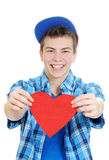 Smiling teenage boy holding valentine heart Stock Photos