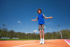Smiling teenage boy jumping the rope outside Stock Photo