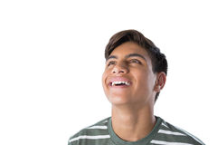 Smiling teenage boy looking away. Against white background Stock Photo