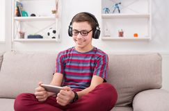 Smiling teenage boy playing mobile game at home. Teenager playing online game on mobile phone and listening to music in earphones at home. Gadget addiction Stock Photo