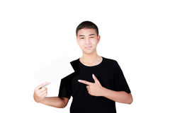 Smiling teenage boy pointing at a blank paper Royalty Free Stock Photography