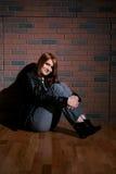 Smiling teenage girl agaist brick wall Stock Image