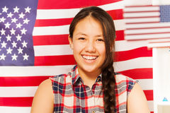 Smiling teenage girl with American flag behind her Stock Images