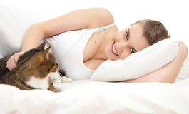 Smiling teenage girl with cat relaxing in white bedding Royalty Free Stock Photography