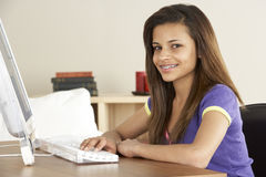 Smiling Teenage Girl on Computer at Home Royalty Free Stock Photos
