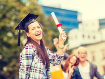 Smiling teenage girl in corner-cap with diploma Royalty Free Stock Images