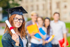 Smiling teenage girl in corner-cap with diploma Stock Photo