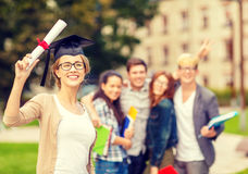 Smiling teenage girl in corner-cap with diploma Royalty Free Stock Image