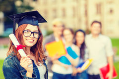 Smiling teenage girl in corner-cap with diploma Royalty Free Stock Photo