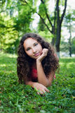 Smiling teenage girl with curly hair lying on a green grass Royalty Free Stock Images