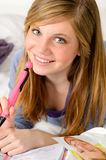 Smiling teenage girl daydreaming over her diary Royalty Free Stock Images