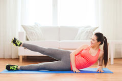 Smiling teenage girl doing exercise for legs Stock Image