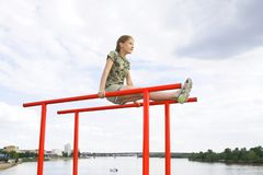 Smiling teenage girl doing gymnastic exercises on uneven bars in city conditions outdoors Royalty Free Stock Image