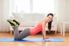 Smiling teenage girl doing push-ups at home. Fitness, home and diet concept - smiling teenage girl doing push-ups at home royalty free stock photos